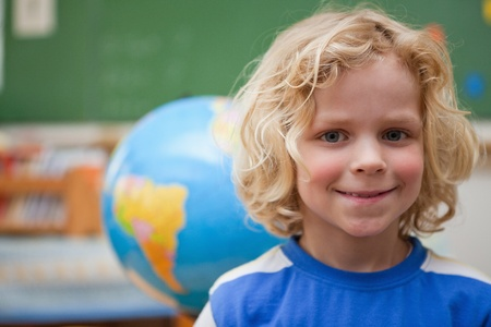 Schoolboy posing in front of a globe in a classroom photo