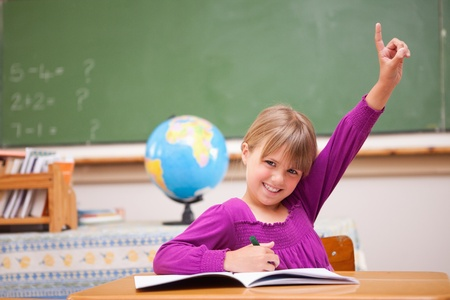 Schoolgirl raising her hand to ask a question in a classroom photo