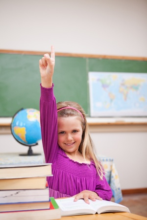 Portrait of young schoolgirl raising her hand in a classroom photo