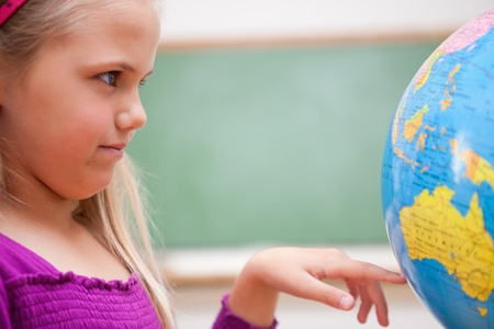 schoolkid search: Close up of a schoolgirl looking at a globe in a classroom Stock Photo