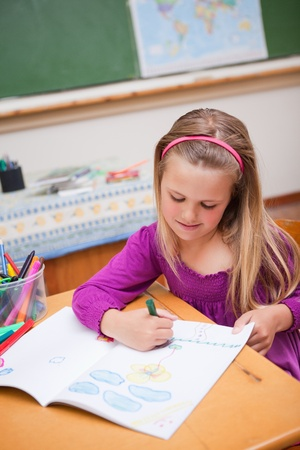 Portrait of a cute schoolgirl drawing in a classroom photo