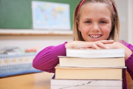 niños estudiando: Colegiala posando con una pila de libros en el aula Foto de archivo