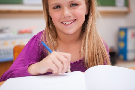 Close up of a young schoolgirl writing in a classroom photo