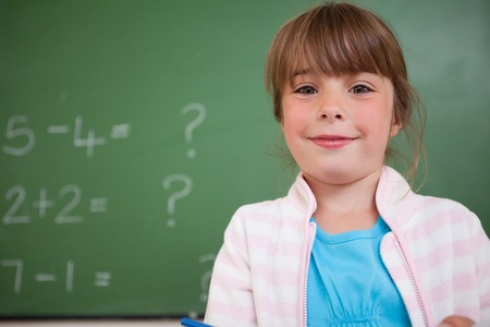 Little girl standing up in front of a blackboard Stock Photo - 11679815