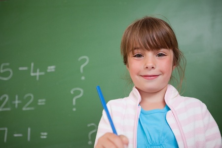 Cute girl holding a pen in front of a blackboard Stock Photo - 11679732
