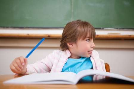 Happy girl holding a pen in a classroom Stock Photo - 11681014