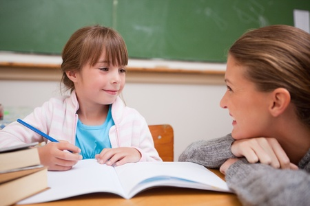 teacher student: A teacher and a schoolgirl talking in a classroom