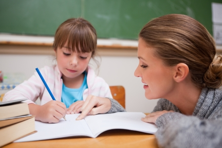 Cute schoolgirl writing a while her teacher is talking in a classroom photo