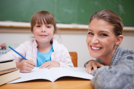 Schoolgirl writing with her teacher in a classroom Stock Photo