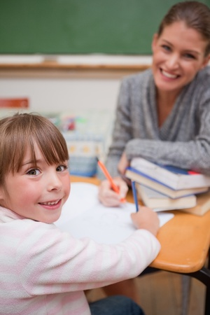 Portrait of a smiling teacher explaining something to her pupil in a classroom photo