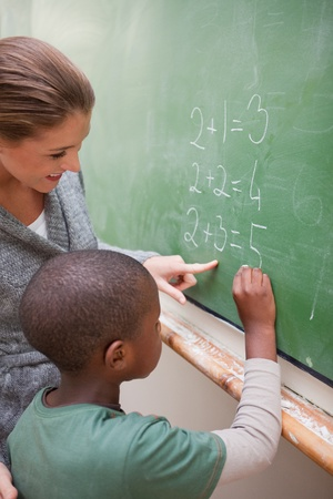 schooling: Portrait of a cute teacher and a pupil making an addition on a blackboard Stock Photo