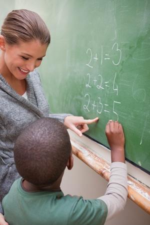 classroom teacher: Ritratto di un insegnante bello e un allievo fare un'aggiunta su una lavagna