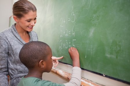 personas ayudando: Lindo maestro y un alumno hacer una adición en una pizarra