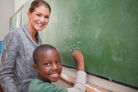 Smiling teacher and a pupil making an addition on a blackboard photo