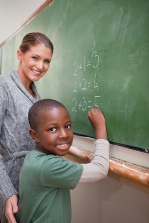 ni�os ayudando: Retrato de un profesor que explica las matem�ticas a un alumno en una pizarra Foto de archivo