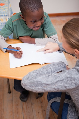 Portrait of a teacher explaining something to a schoolboy in a classroom photo