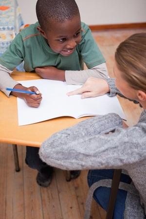 tutor: Retrato de un profesor explicando algo a un alumno en un aula Foto de archivo