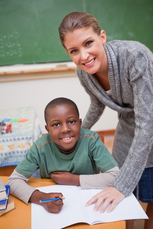 Portrait of a teacher explaining something to a smiling schoolboy in a classroom photo