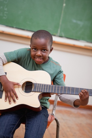 music instrument: Portrait of a schoolboy playing the guitar in a classroom Stock Photo