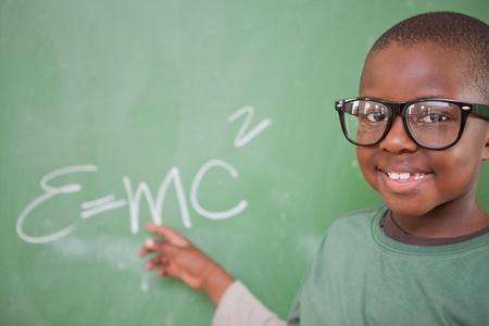 equivalence: Smart schoolboy showing the mass-energy equivalence on a blackboard