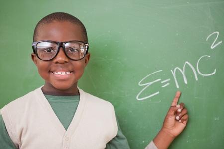 niños negros: Colegial que muestra la fórmula de la equivalencia masa-energía en una pizarra Foto de archivo