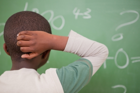 Schoolboy thinking with his hand on his head in front of a blackboard photo