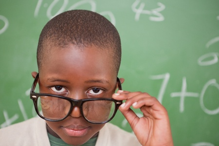 Schoolboy looking over his glasses in front of a blackboard photo