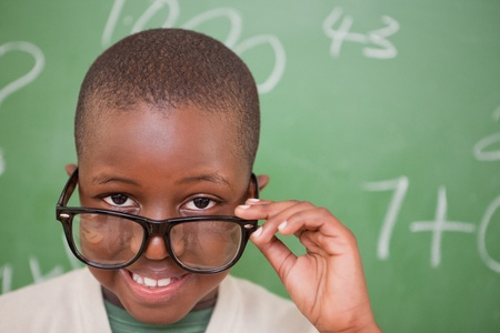 Smiling schoolboy looking over his glasses in front of a blackboard photo