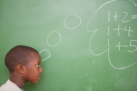 Schoolboy thinking about additions in front of a blackboard photo