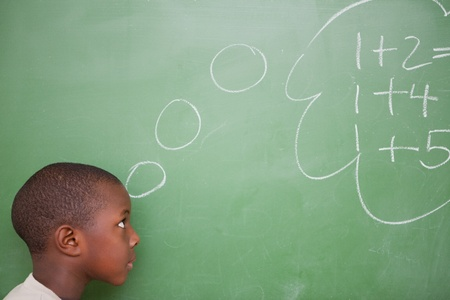 Smart schoolboy thinking about additions in front of a blackboard photo
