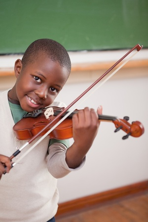 Portrait of a boy playing the violin in a classroom photo