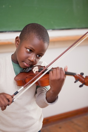 violins: Portrait of a schoolboy playing the violin in a classroom Stock Photo