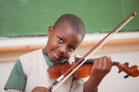violin: Schoolboy playing the violin in a classroom Stock Photo