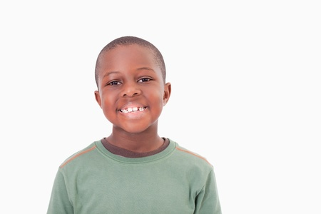 child model: Smiling boy posing against a white a background