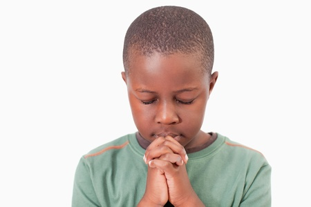 worship white: Young boy praying against a white background