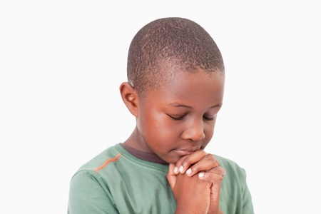 christian faith: Calm boy praying against a white background