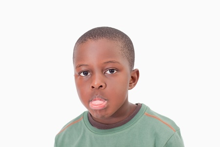 Boy sticking out his tongue against a white background
