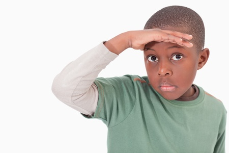 far away look: Boy putting his hand on his forehead against a white background