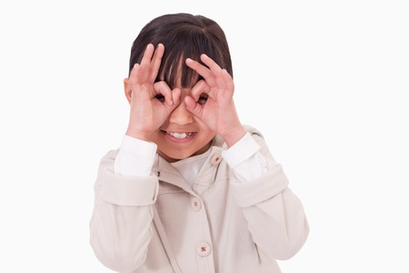 Girl putting her fingers around her eyes against a white background photo