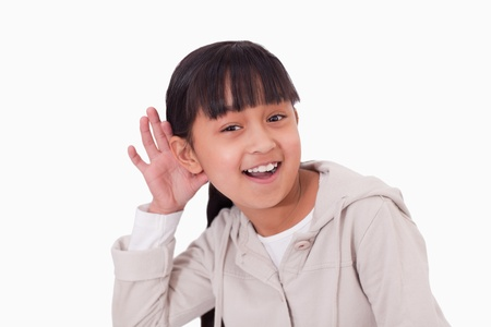 Girl pricking up her ear against a white background photo