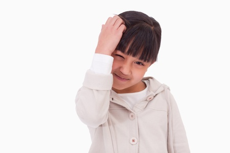 scratching head: Cute girl thinking against a white background