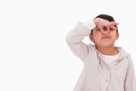 pinching: Girl pinching her nose against a white background