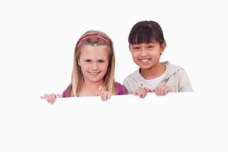 Girls behind a blank panel against a white background photo