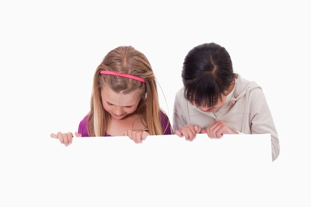 Girls looking at a blank panel against a white background photo