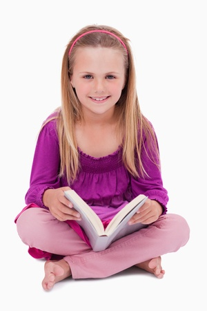 Portrait of a happy girl reading a book against a white background photo