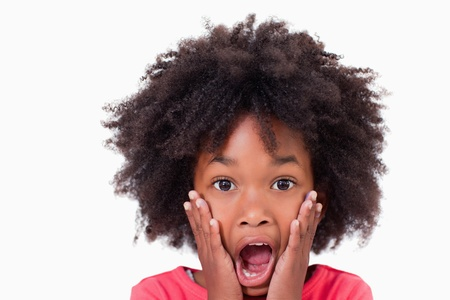 surprised child: Close up of a shocked girl against a white background