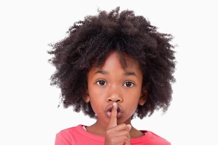 Close-up van een meisje te vragen stilte tegen een witte achtergrond