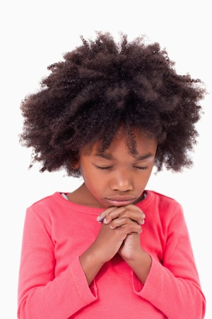 christian worship: Portrait of a girl praying against a white background