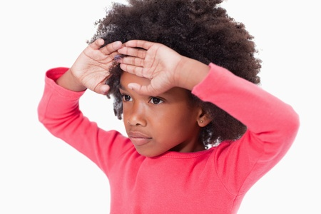 affliction: Girl with her hands on her forehead against a white background