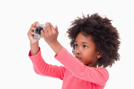 Cute girl taking a picture against a white background photo